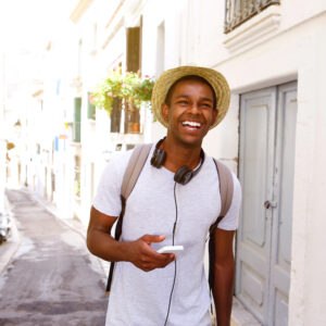 Portrait of a happy male traveler walking in town with mobile phone and bag